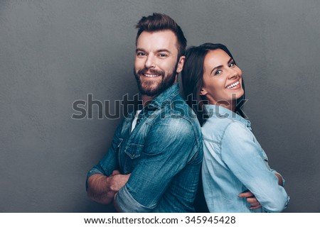 Happy loving couple. Studio shot of beautiful young couple in jeans wear standing back to back and smiling  #345945428