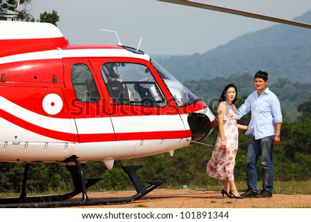 Happy loving couple traveling by helicopter and smiling