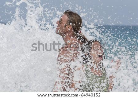 Happy loving couple under splashes of sea waves