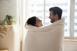 Happy loving couple wrapped in white warm blanket hugging, standing in kitchen at home, smiling beautiful wife and handsome husband looking at each other, enjoying tender moment, having fun