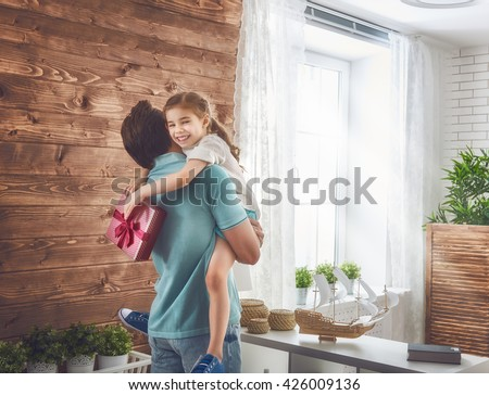 Happy loving family and Father\'s Day. Father and his daughter. Cute child girl gives a gift to dad.