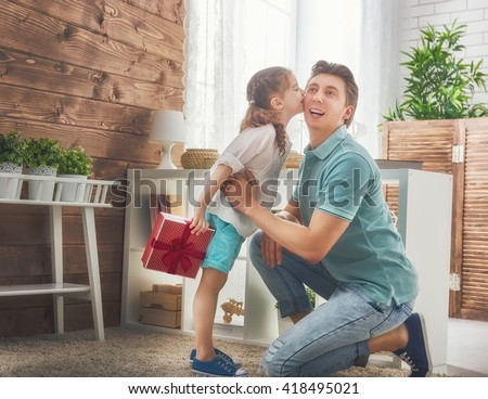 Happy loving family and Father's Day. Father and his daughter. Cute child girl kisses dad and gives him a gift.