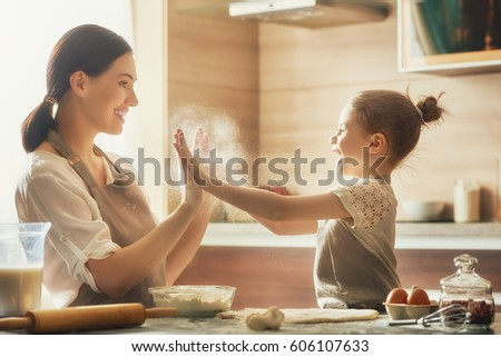Happy loving family are preparing bakery together. Mother and child daughter girl are cooking cookies and having fun in the kitchen. Homemade food and little helper. #606107633