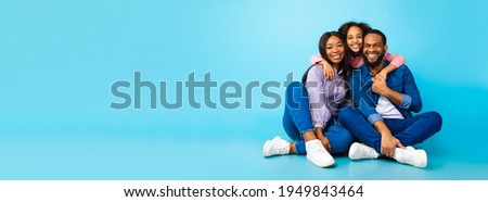 Happy Loving Family. Black man, woman and girl sitting on the floor isolated on blue studio wall. Smiling daughter emracing her mum and dad from behind, posing at camera, banner, panorama, copy space Foto stock ©