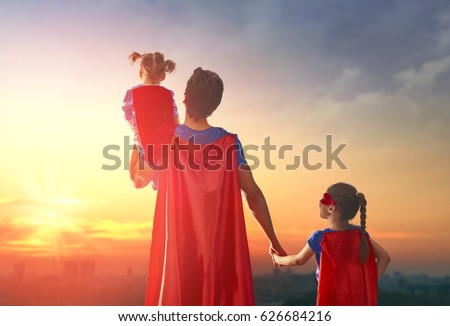 Happy loving family. Dad and his daughters are playing outdoors. Daddy and his children girls in an Superhero's costumes. Concept of Father's day. #626684216