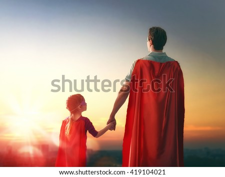 Happy loving family. Father and his daughter child girl playing outdoors. Daddy and his child girl in an Superhero\'s costumes. Concept of Father\'s day.