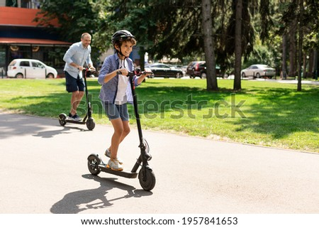 Happy Loving Family. Full body length photo of excited curly boy in protective helmet driving motorized push scooter with daddy at park, spending time together outdoors at summer, selective focus