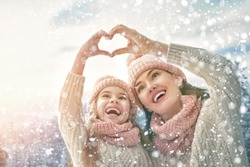 Happy loving family! Mother and child girl having fun, playing and laughing on snowy winter walk in nature. Frost winter season. Mom and kid making hand heart in evening.