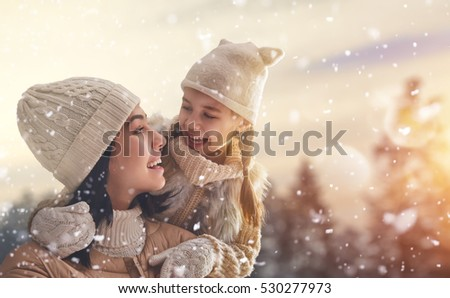 Happy loving family! Mother and child girl having fun, playing and laughing on snowy winter walk in nature. Frost winter season.
