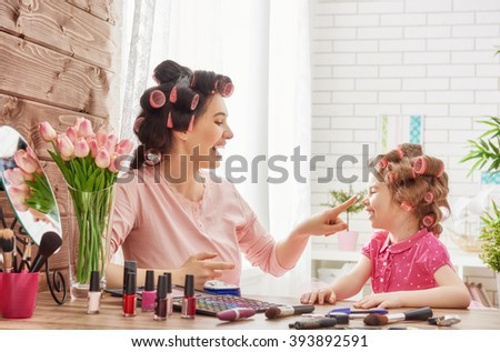 Shutterstock Happy loving family. Mother and daughter are doing hair, manicures, doing your makeup and having fun. Mother and daughter sitting at dressing table at house.