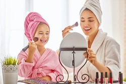 Happy loving family. Mother and daughter are doing make up and having fun sitting at dressing table at home. Mom and child girl are in bathrobes and with towels on their heads.
