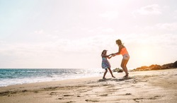 Happy loving family mother and daughter having fun on the beach at sunset - Mum playing with her kid next sea in holidays - Parent, vacation, family lifestyle concept