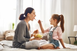 Happy loving family. Mother and her daughter child girl are eating salad on the bed in the room.