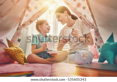 Shutterstock Happy loving family. Mother and her daughter girl play tea-party and drink tea from cups in children room. Funny mom and lovely child having fun indoors.
