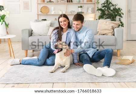 Happy Loving Family. Portrait of beautiful spouses patting dog sitting on the floor carpet in modern apartment