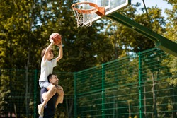 Happy Loving Family. Portrait of young curly boy sitting on father's shoulders, playing basketball, throwing ball to basket, man standing on court outdoors and helping his son, selective focus
