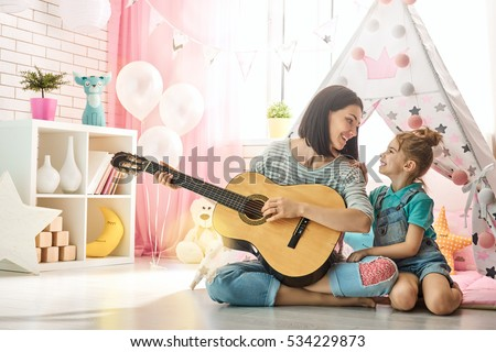 Happy loving family. Pretty young mother and daughter playing guitar together. Adult woman playing guitar for child girl indoors. Funny mom and lovely child having fun in children room.