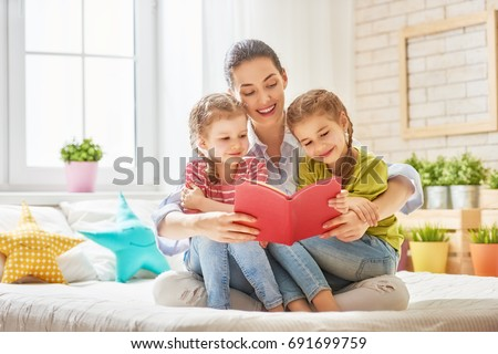 happy loving family. pretty young mother reading a book to her daughters #691699759