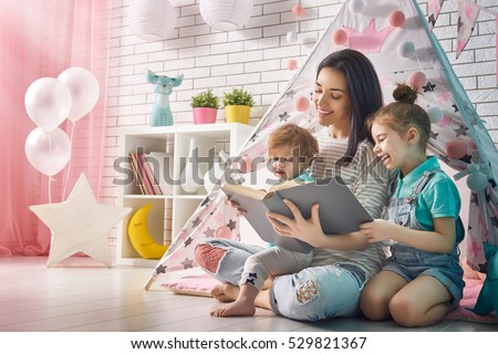 Happy loving family. Pretty young mother reading a book to her daughters indoors. Funny mom and lovely child having fun in children room. #529821367