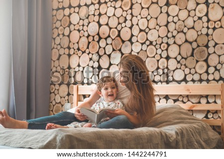 Happy loving family. Pretty young mother reading a book to her little son in modern interior #1442244791