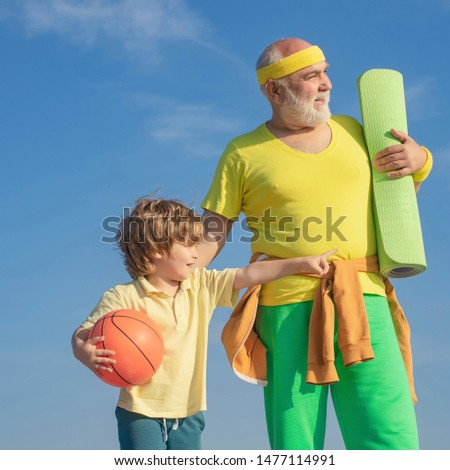 Happy loving family. Sportsman grandfather and healthy kid with basketball ball on blue sky background. Sport for little children