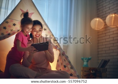 Happy loving family. Young mother and her daughter girl play in children room at the bedtime. Funny mom and lovely child are having fun with tablet.