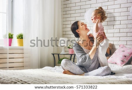 Happy loving family. Young mother are playing with her baby girl in the bedroom. Mom and child are having fun on the bed. #571333822