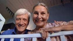 Happy loving grandparents talking to newborn grandchild in blue crib. Bottom view of smiling grandmother and grandfather looking at sleeping baby in cradle