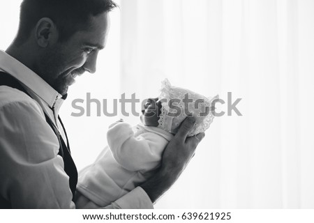 Happy loving handsome father holds his small newborn daughter. Profile backlit black and white picture.