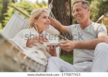 Happy loving man and woman are spending time together with hot drinks in yard of holiday home