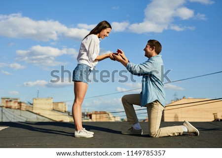 Happy loving man getting on one knee and opening jewelry box with engagement ring while making marriage proposal to beautiful woman on city roof