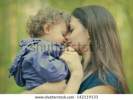 Happy loving mother and baby girl embracing outdoor summer background. Closeup portrait