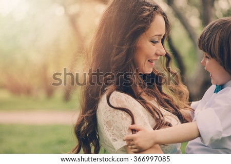 happy loving mother with toddler son on the walk in sunny park. Family spending time together in spring or summer. Cozy warm mood.
