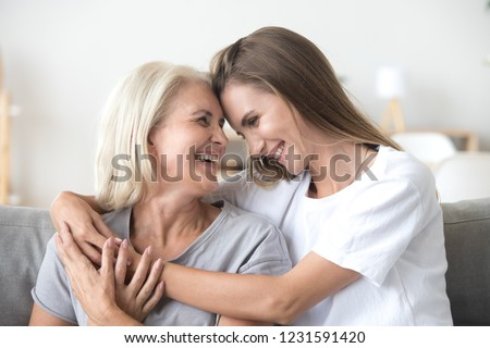 Happy loving older mature mother and grown millennial daughter laughing embracing, caring smiling young woman embracing happy senior middle aged mom having fun at home spending time together #1231591420