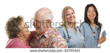 Happy Loving Senior Couple with Smiling Medical Doctors or Nurses Behind Isolated on a White Background. - stock photo