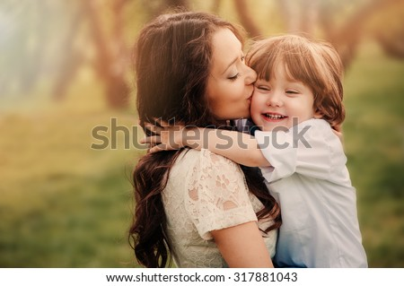 happy loving young mother kisses her toddler son on the walk