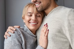 Happy loyal woman with closed eyes leaning on chest of reliable man while spending time at home