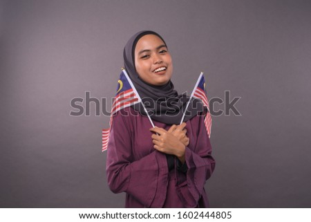 Happy Malaysian girl holding Malaysia Flag.Independence Day and patriotic concept.Studio shot.