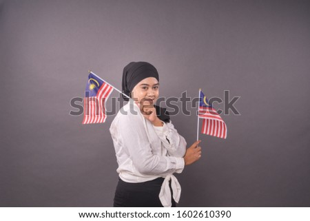 Happy Malaysian Girl holding Malaysia Flag.Independence Day and Patriotic concept studio shot.