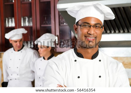 happy male african professional chefs in industrial kitchen with colleagues behind