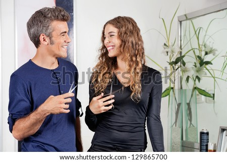 Happy male and female hairdressers looking at each other in salon