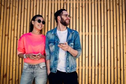 Happy male and female influence bloggers standing near promotional background and smiling, sincerely hipster guys using cellphone gadgets for network browsing on leisure, concept of pda technology