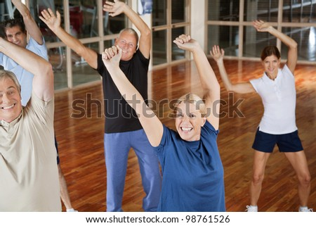 Happy male and female seniors dancing to music in gym