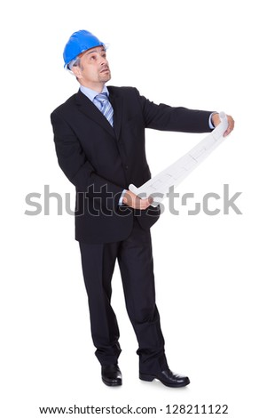 Happy Male Architect Looking At Blueprint On White Background