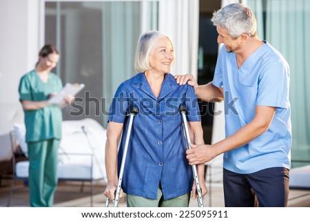 Happy male caretaker helping senior woman in walking with nurse in background at nursing home yard