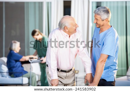Happy male caretaker looking at disabled senior man at nursing home yard Stock foto ©