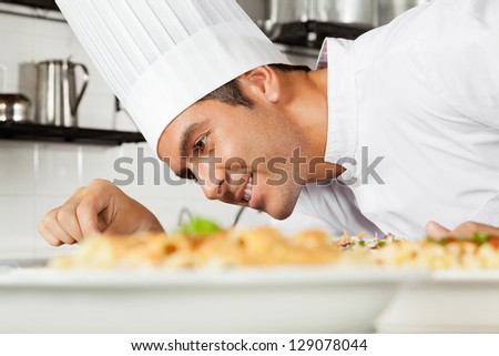 Happy male chef garnishing dish in commercial kitchen