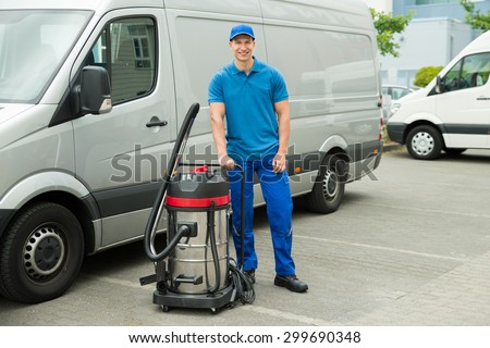 Happy Male Cleaner In Blue Uniform Standing With Vacuum Cleaner #299690348