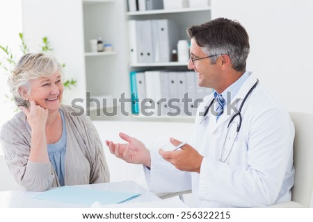 Happy male doctor discussing with senior patient at table in clinic