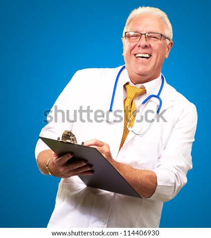 Happy Male Doctor Writing On Clipboard Isolated On Blue Background